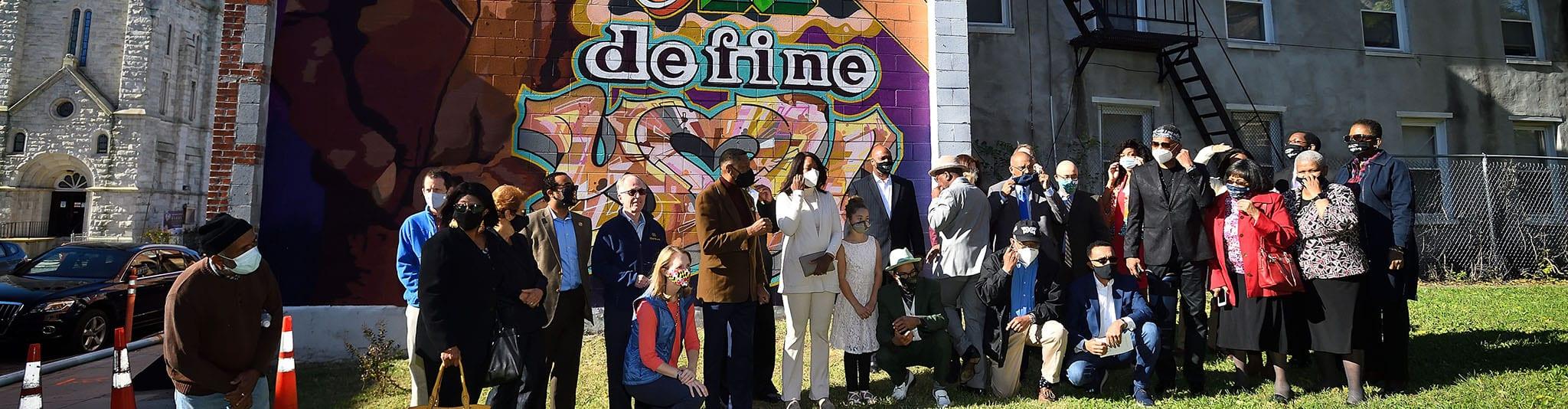 people in front of Elijah Cummings mural